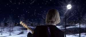 View of Dr. Billy Mack with guitar from the back. He looks over a snowy scene in the moonlight.
